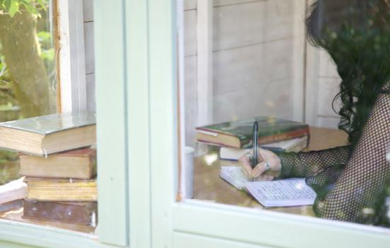 a female writing at a desk behind a glass door