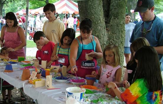 Children painting at an outdoor table