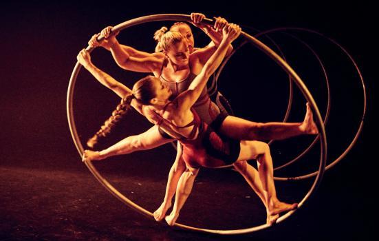 Photo of three circus performers in large hoop