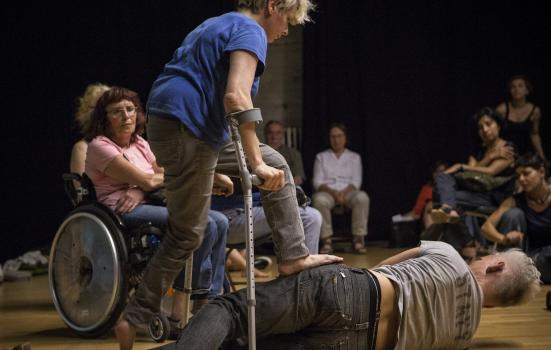 Photo of woman with crutches on stage standing over actor lying down