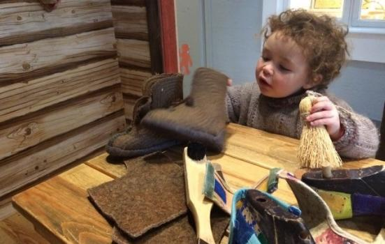 Photo of young child playing with shoes in cobblers shop
