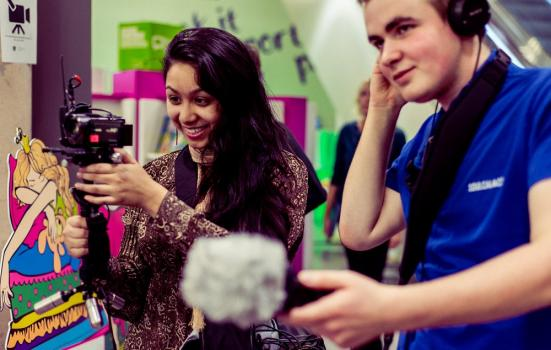 Photo of two young people filming
