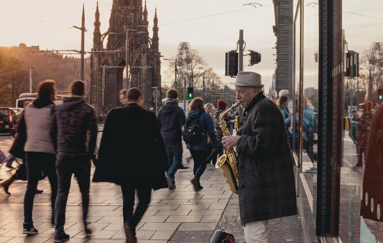 Edinburgh Conversations: it's time to redefine culture at local level. This image shows a man playing a saxophone on an Edinburgh street with people walking by