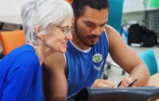 Photo of woman watching younger man writing
