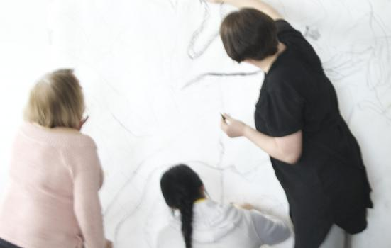 Photo of three women drawing on a white wall