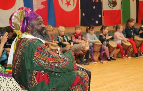 Photo of workshop leader drumming with young school children