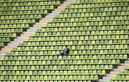 Photo of a man sitting in an empty stadium