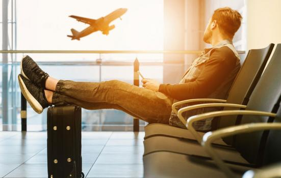 Photo of a man sitting in an airports, watching a plane take off