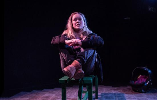 Photo of actor sitting on a bench, dimly lit stage, during in a monologue