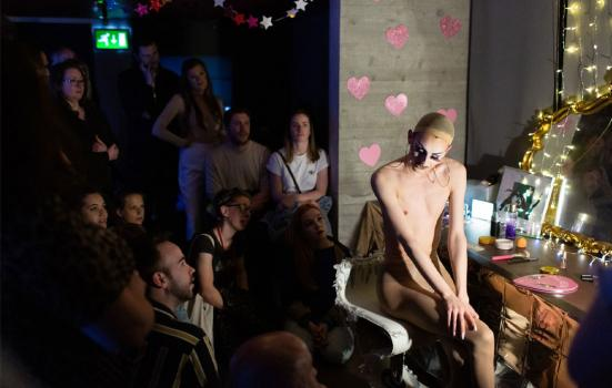 Photo of a transgender person getting ready at a vanity table as a audience watches on.