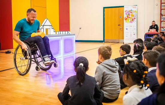 A man in a wheelchair performing for a group of young children