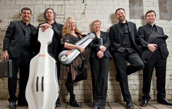 A photo of a band, with orchestral instruments in case, dressed in black against a white tiled wall.