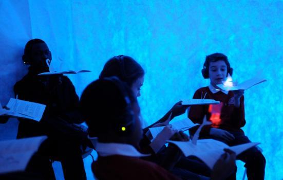 Photo of a group of children wearing headset, interacting with a book