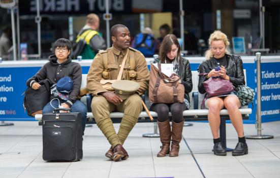 A photo of an Asian women with a suitcase, a Black service man and two white women on their phones sitting on a bench in a station