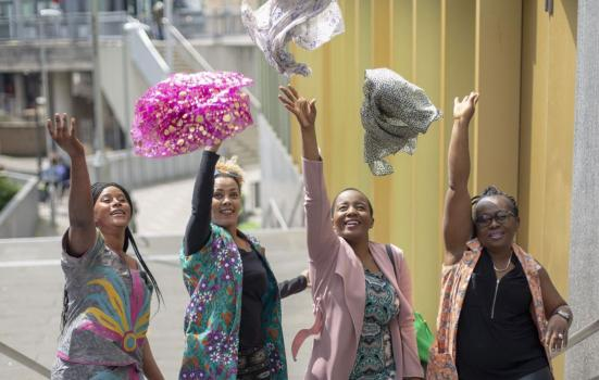 Photo of four women throwing scarfs into the air