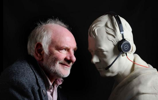 Photo of Tom Pow staring face to face with a sculpture which is wearing headphones