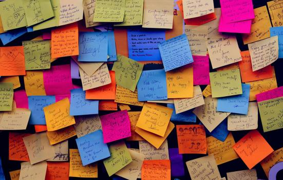 Photo of a board covered in multicoloured Post-it notes