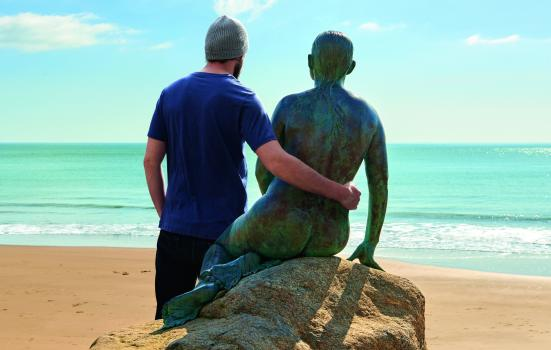 Photo of man on beach with arm round sculpture
