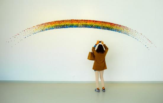 Woman taking a photo of an art installing depicting a rainbow