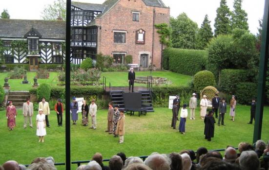 A photo of a theatrical performance in the grounds of a country house