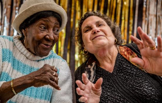 Photo of two older women posing on stage