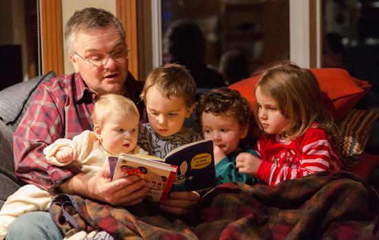 Photo shows a grandfather reading bedtime stories to three toddlers and a baby on a sofa