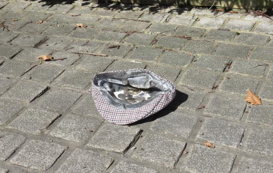 A hat full of coins on a street