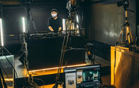 DJ live streaming a performance wearing a surgical facemask
