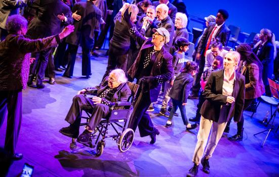 casual group of people on a stage with an elderly person in a wheelchair in the foreground