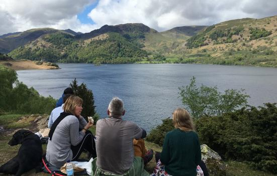 Photo of people sitting by lake
