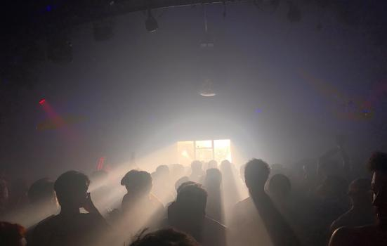 Silhouettes of a crowd cast by club lights