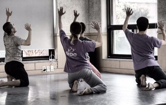 Photo of three dancers rehearsing