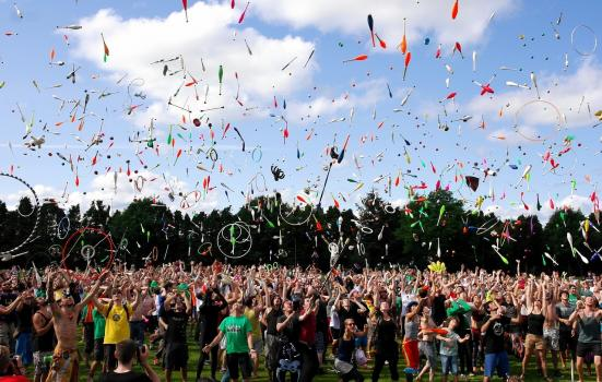 A photo of a large group of people throwing juggling clubs and hoops in the air