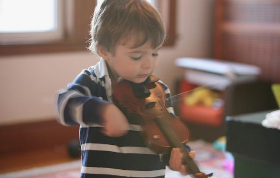 A young boy with a micro violin