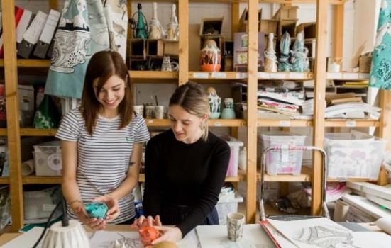 Photo of two women looking at ceramics in a store room