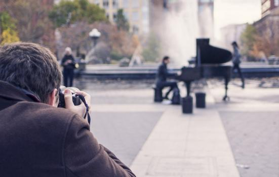 A photo of a man photographing a street piano player