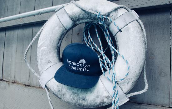 "a baseball cap lodged in a life buoy on a boat. The caption on the hat is ""harmonize humanity"""