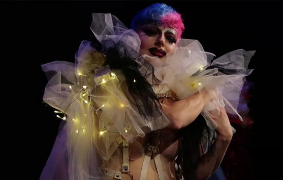 Photo of an actor draped on translucent fabric and fairy lights