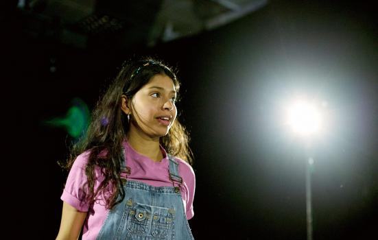 a girl standing on stage in a spotlight