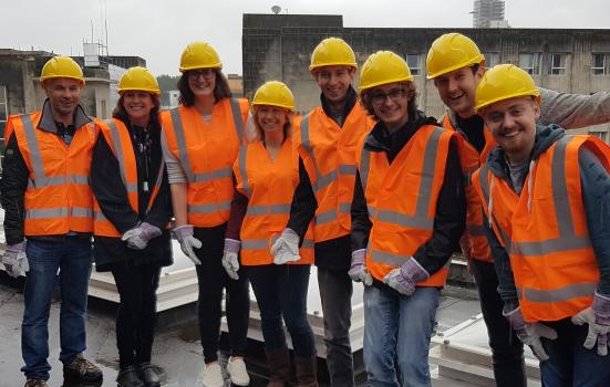 Photo of people in high-vis on rooftop