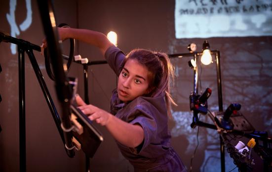A woman leaning to her left, configuring light rigging.