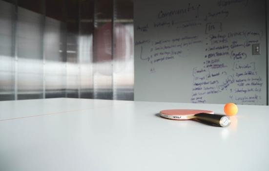 A photo of a ping pong bat on a table by a whiteboard