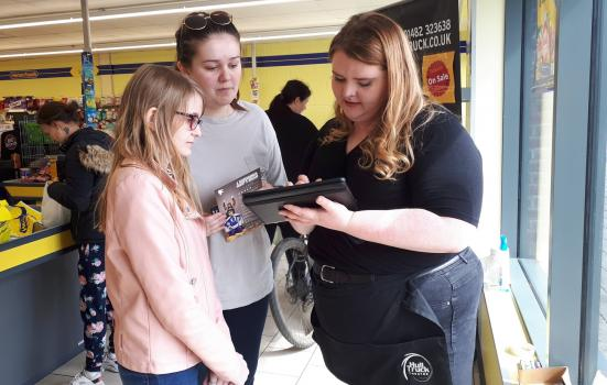 Photo of three people looking at ipad in supermarket