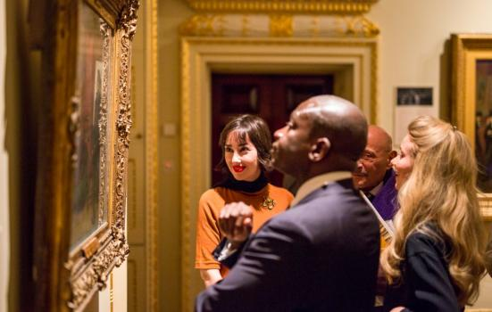 Photo of people looking at a painting in gallery