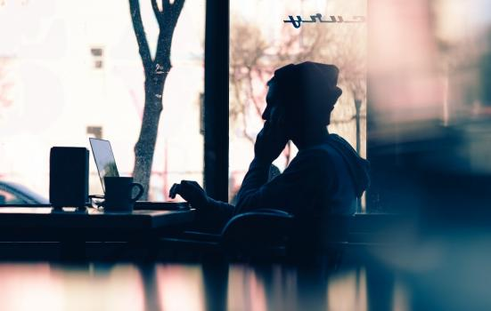 Photo of man on laptop in cafe