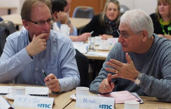 Photo of two men in discussion in workshop