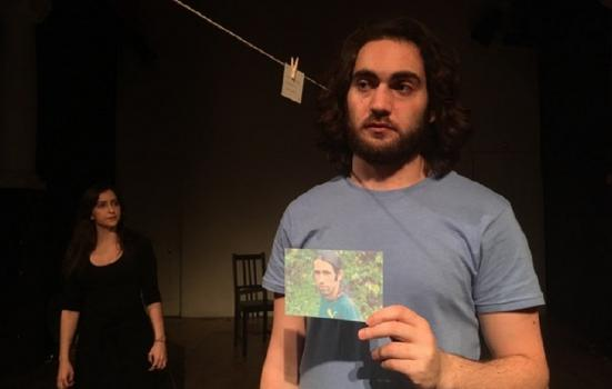 A man holding a photo with a woman in the background
