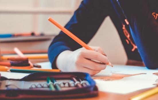 A pupil at a desk holidng a pencil