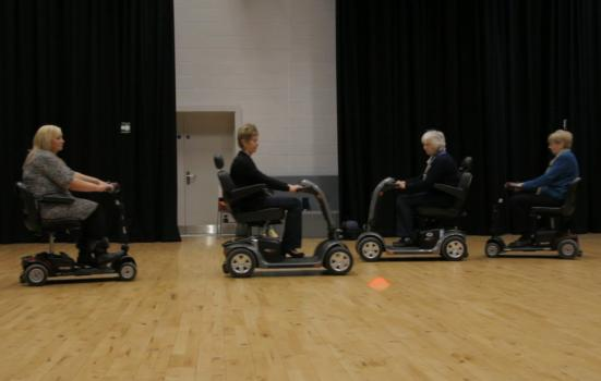 Photo of people rehearsing a dance in mobility scooters