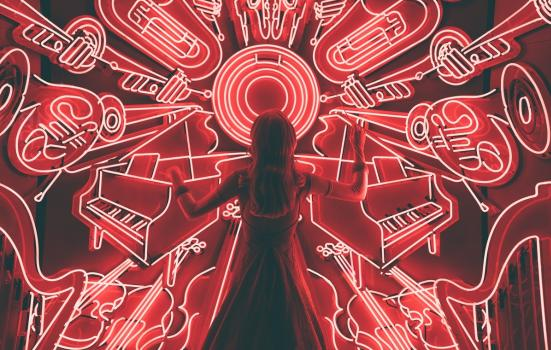 Woman stsanding in front of neon red lights in the shap of muscial instruments